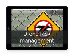 Tablet showing image of the sign on the fence prohibiting drone activity